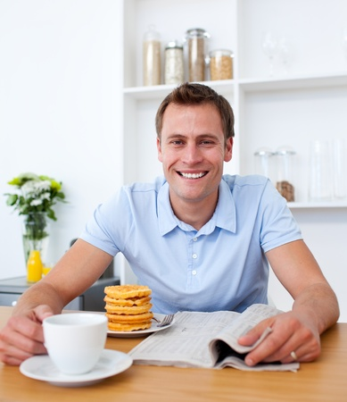 Attractive man reading a newspaper while having breakfast photo