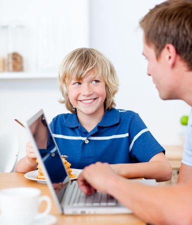 Cute boy having breakfast while his father using a laptop photo