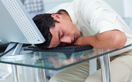 afflict: Tired businessman sleeping at his desk