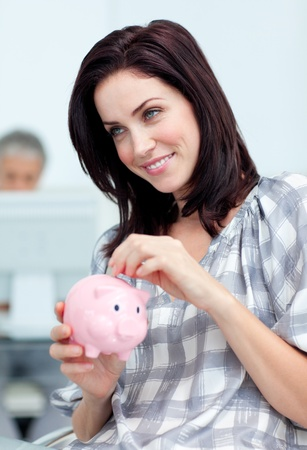 Delighted businesswoman saving money in a piggy-bank photo