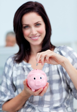 corporate greed: Charismatic businesswoman saving money in a piggy-bank