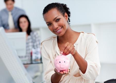 Confident businesswoman saving money in a piggy-bank photo