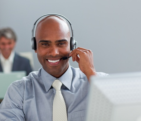 Charismatic  businessman with headset on working at a computer photo