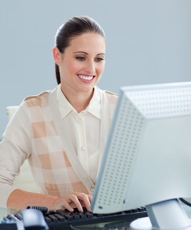 Delighted businesswoman working at a computer  photo