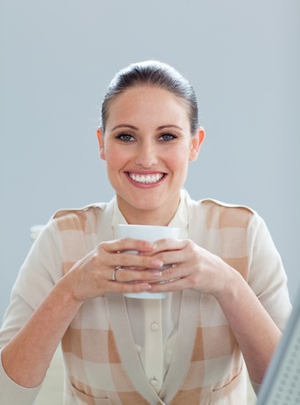 Delighted businesswoman drinking a coffee photo