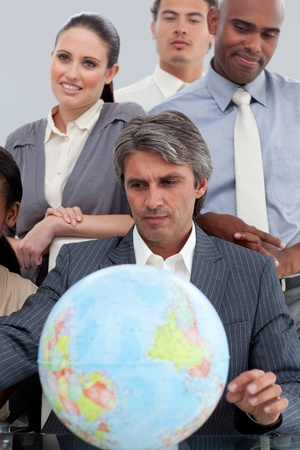 Multi-ethnic business people around a terrestrial globe photo