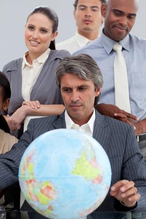Multi-ethnic business people around a terrestrial globe photo