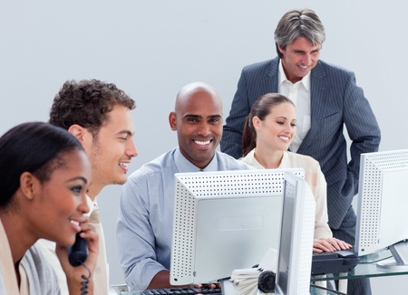 teaming: Positive business group working hard in the office Stock Photo
