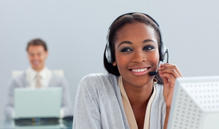 Radiant businesswoman using headset at her desk photo