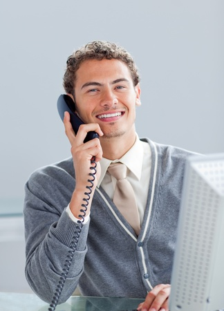 Smiling businessman on phone at his desk photo