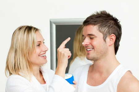 Wife putting cream on his husband's nose Stock Photo - 10097289