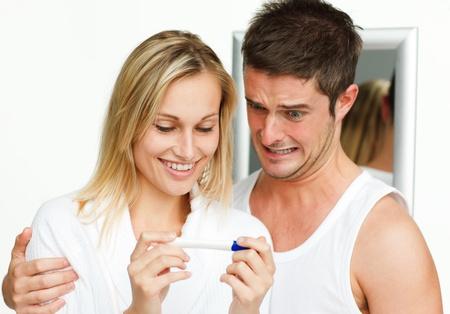 prueba de embarazo: Mujer feliz y hombre asustado examinar una prueba de embarazo Foto de archivo