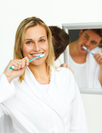 Smiling woman cleaning her teeth with her boyfriend  photo