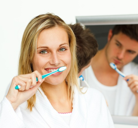 Portrait of an attractive woman cleaning her teeth with her boyfriend photo