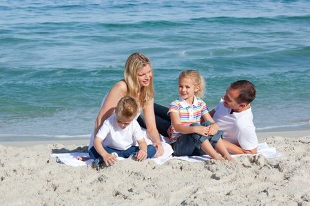 Caring parents with their children sitting on the sand photo