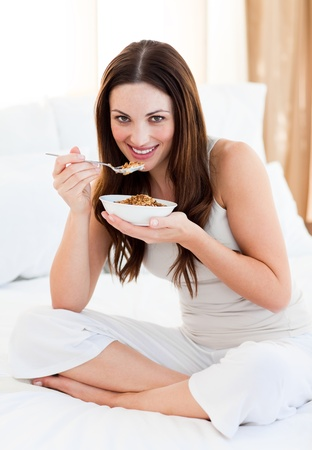 Attractive woman eating cereals sitting on bed photo