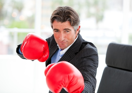 Competitive businessman wearing boxing gloves photo
