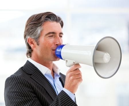 Confident businessman yelling through a megaphone photo