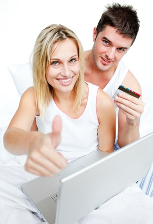 Couple in bed buying on-line with thumb up Stock Photo - 10097221