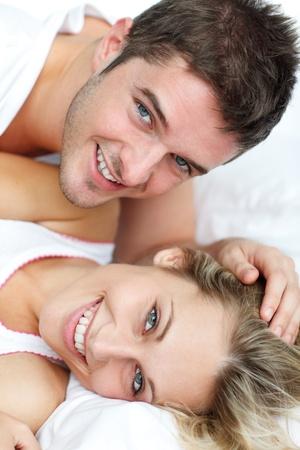 pareja apasionada: Amantes sonrientes tumbado en la cama