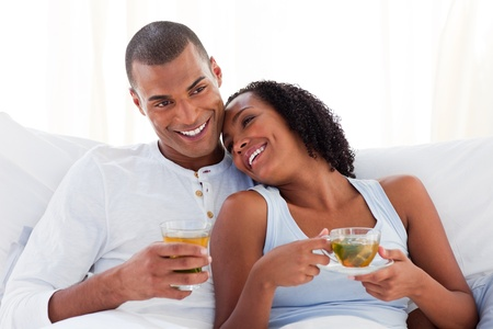 Happy ethnic couple drinking a cup of tea on their bed photo