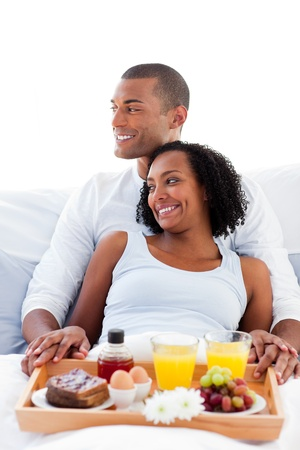 Enamoured couple having breakfast lying on their bed photo