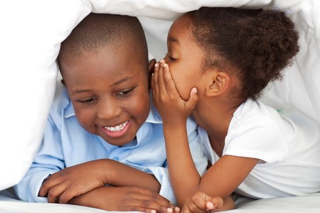 Ethnic little girl whispering something to her brother photo