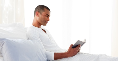 Concentrated man reading lying on his bed Stock Photo - 10095137