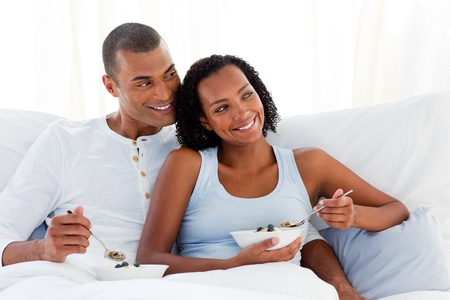 Cheerful couple having breakfast on their bed photo