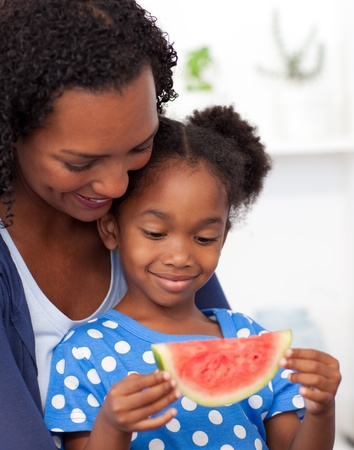 Beautiful girl eating watermelon with her mother photo
