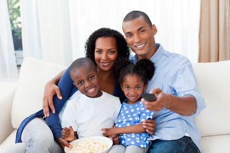 Smiling Afro-american family eating popcorn and watching TV Stock Photo - 10097436