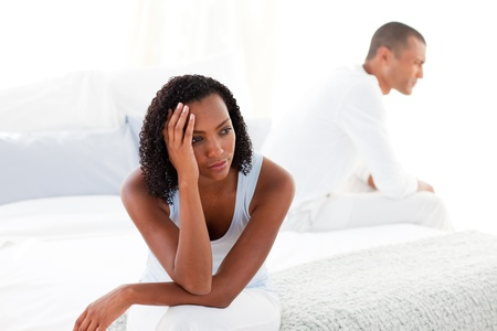 disagreement: Upset young couple sitting on bed separately Stock Photo