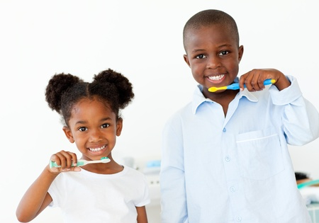 Smiling brother and sister brushing their teeth  photo