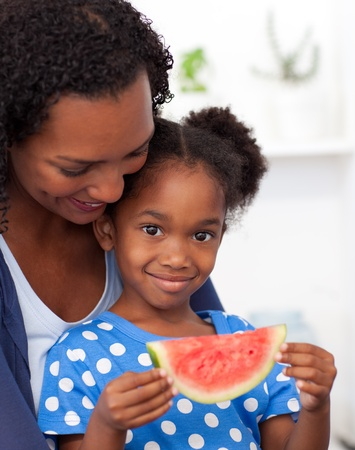 Portrait of a smiling girl eating fruit  photo