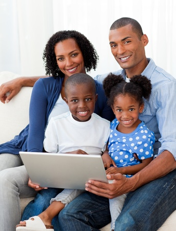 Smiling Afro-american family using a laptop photo