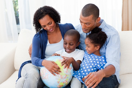 Happy family holding a terrestrial globe photo