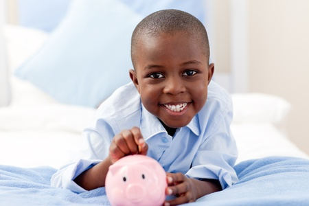 piggy bank money: Young boy smiling at the camera