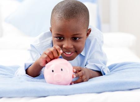 piggy bank money: Young Boy on a bed putting money into a piggy bank