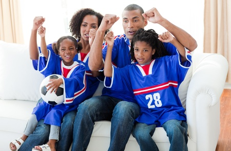 Excited Afro-American family watching a football match photo