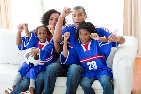 Afro-American family celebrating a goal at home photo