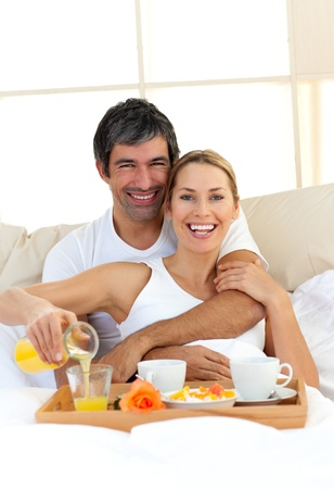Romantic couple having breakfast lying in the bed photo