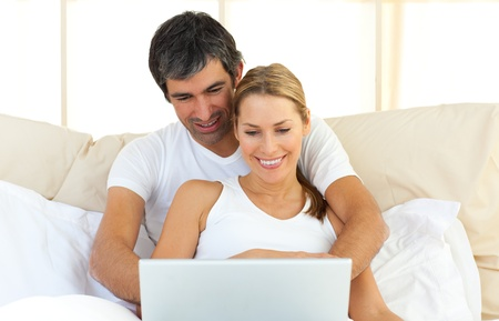 Enamoured couple using a laptop lying in the bed photo