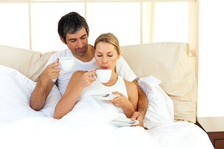 Jolly couple drinking coffee lying in the bed photo