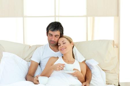 mujer tomando cafe: Par positivo beber caf� tumbado en la cama