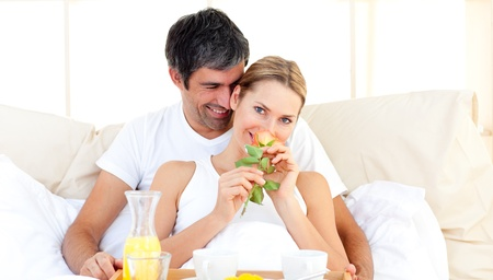 Caucasian couple having breakfast lying in the bed photo