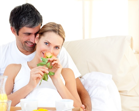 Close-up of couple having breakfast lying in the bed photo
