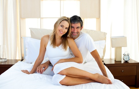 Affectionate lovers embracing on bed photo