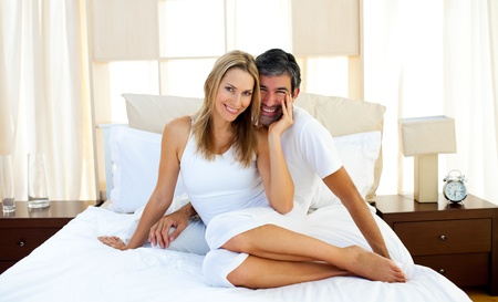 Portrait of lovers sitting on bed photo