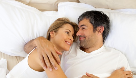 Affectionate couple hugging lying in bed photo