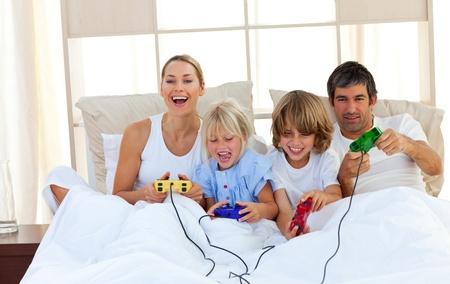 ni�os jugando videojuegos: Amante de la familia jugando videojuegos en el dormitorio Foto de archivo